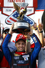 Ty Majeski poses with the trophy in Victory Lane after winning the ARCA Series auto race at Pocono Raceway, Friday, May 31, 2019, in Long Pond, Pa. (AP Photo/Matt Slocum)
