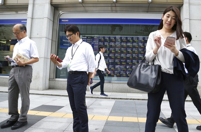 In this Sept. 11, 2018, photo, people use smartphones in front of an electronic stock board of a securities firm in Tokyo. Asian shares were mostly higher Wednesday, Sept. 19, 2018, despite jitters over the escalating trade dispute between the U.S. and China. (AP Photo/Koji Sasahara)