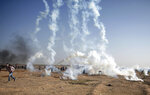 """FILE - In this Tuesday, May 15, 2018 file photo, Palestinian protesters run from teargas fired by Israeli troops at the Gaza Strip's border with Israel. The aftershocks of the U.S. Embassy move to Jerusalem and bloodshed on the Gaza border are shaking up the region, including the relationship between Palestinian President Mahmoud Abbas and former his negotiating partners, Israel and the U.S. Seething over a perceived U.S. betrayal on Jerusalem, Abbas is preparing to pursue what has been called his """"doomsday weapon,"""" a war crimes complaint against Israel at the International Criminal Court. (AP Photo/Khalil Hamra, File)"""