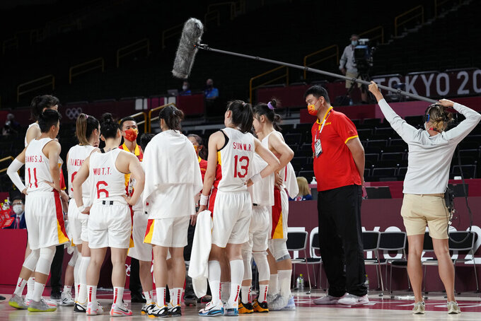 China's Yao Ming, second from right, stands in the huddle with the women's team during a timeout in a women's basketball quarterfinal game against Serbia at the 2020 Summer Olympics, Wednesday, Aug. 4, 2021, in Saitama, Japan. (AP Photo/Eric Gay)