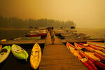 A business owner, who declined to give his name, walks next to kayaks he rents as smoke from the Creek Fire fills the sky, Sunday, Sept. 6, 2020, in Shaver Lake, Calif. (AP Photo/Marcio Jose Sanchez)