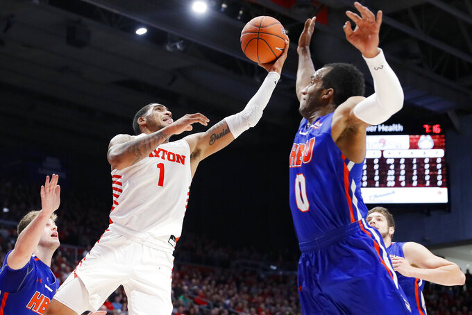 Dayton's Obi Toppin (1) shoots against Houston Baptist's Ian DuBose (0) during the first half of an NCAA college basketball game, Tuesday, Dec. 3, 2019, in Dayton, Ohio. (AP Photo/John Minchillo)