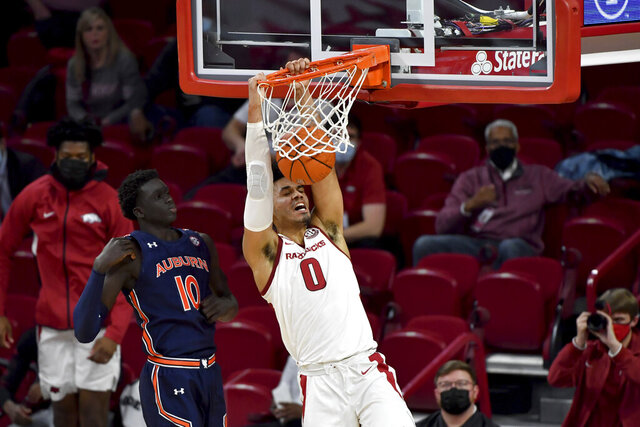 Arkansas forward Justin Smith (0) dunks in front of Auburn defender JT Thor (10) during the second half of an NCAA college basketball game Wednesday, Jan. 20, 2021, in Fayetteville, Ark. (AP Photo/Michael Woods)