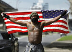 A protester holds up an American flag as about a dozen people gather on the corner of Esplanade Ave. and N. Claiborne Ave., Friday, May 29, 2020, in New Orleans, La.,  to protest the death of George Floyd, a handcuffed black man who died in police custody after he pleaded for air as a white police officer kneeled on his neck in Minneapolis. (Max Becherer/The Times-Picayune/The New Orleans Advocate)