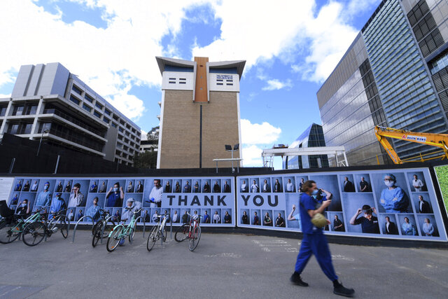 A man wearing a face mask walks past an outdoor photography exhibition of healthcare workers in Melbourne, Tuesday, Sept. 22, 2020. The photo essay created by photographer Phoebe Powell is to acknowledge the people working in the Parkville Biomedical Precinct which is home to some of the world's leading medical researchers, clinicians and academics keeping Victoria state safe during the coronavirus pandemic. (James Ross/AAP Image via AP)
