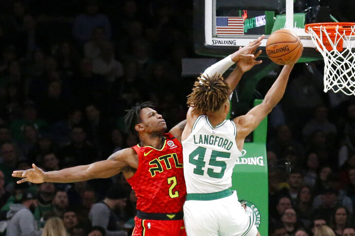 Atlanta Hawks guard Treveon Graham (2) tries to block a shot by Boston Celtics guard Romeo Langford (45) during the second half of an NBA basketball game Friday, Feb. 7, 2020, in Boston. (AP Photo/Mary Schwalm)