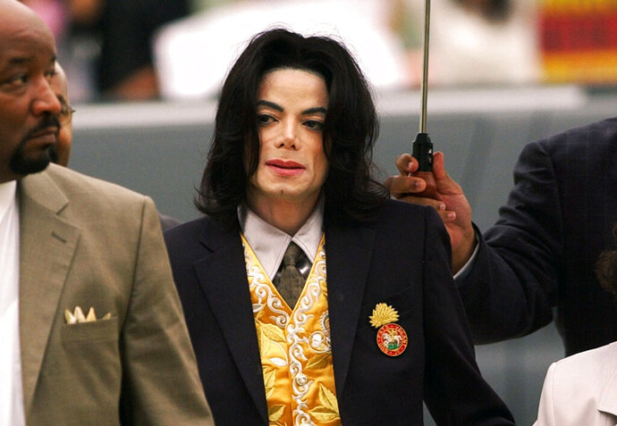 FILE - In this May 25, 2005 file photo, Michael Jackson arrives at the Santa Barbara County Courthouse for his trial in Santa Maria, Calif. A settlement has been reached in a lawsuit between Tohme Tohme, a former manager of Michael Jackson, and his estate. The settlement announced Thursday, May 23, 2019, ends one of the last remaining legal fights involving Jackson's estate and comes just short of the 10th anniversary of the pop superstar's death. (Aaron Lambert/Santa Maria Times via AP, Pool)