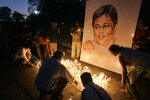 FILE- In this Jan. 15, 2009 file photo, activists and members of Sri Lankan civil societies light candles in front of a portrait of Sunday Leader newspaper editor Lasanthe Wickrematunge in a silent vigil condemning his killing, in Colombo, Sri Lanka. Forced to flee their country a decade ago to escape allegedly state-sponsored killer squads, Sri Lankan journalists living in exile doubt they'll be able to return home soon or see justice served to their tormentors _ whose alleged ringleader could come to power in this weekend's presidential election. Exiled journalists and media rights groups are expressing disappointment over the current government's failure in punishing the culprits responsible for crimes committed against media members. (AP Photo/Gemunu Amarasinghe, File)