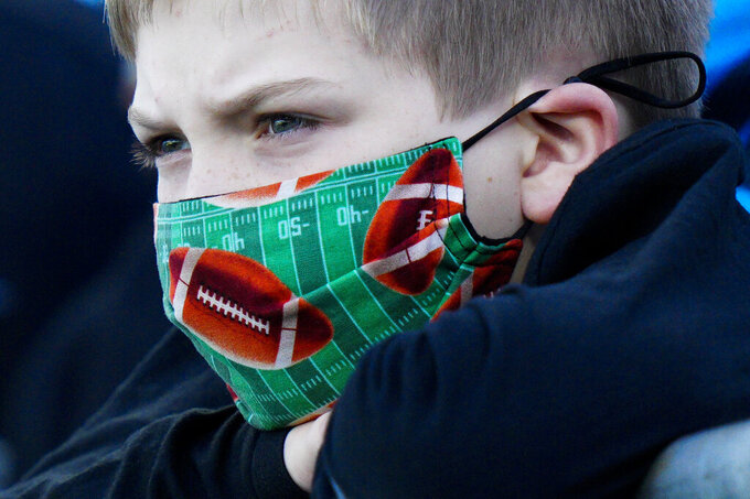 A fan wearing a football face mask watches during warm ups before an NFL football game between the Carolina Panthers and the Philadelphia Eagles Sunday, Oct. 10, 2021, in Charlotte, N.C. (AP Photo/Jacob Kupferman)