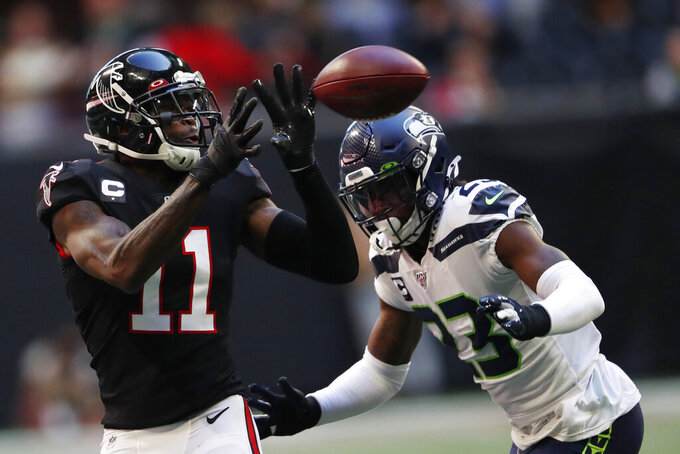 of Seattle Seahawks defensive back Neiko Thorpe (23) Atlanta Falcons wide receiver Julio Jones (11) makes the catch ahead during the first half of an NFL football game, Sunday, Oct. 27, 2019, in Atlanta. (AP Photo/John Bazemore)