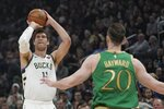 Milwaukee Bucks' Brook Lopez shoots a three-point basket in front of Boston Celtics' Gordon Hayward during the first half of an NBA basketball game Thursday, Jan. 16, 2020, in Milwaukee. (AP Photo/Morry Gash)