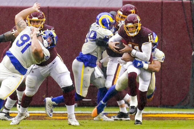 Washington Football Team's Alex Smith is sacked by Los Angeles Rams' Troy Reeder during the second half of an NFL football game Sunday, Oct. 11, 2020, in Landover, Md. (AP Photo/Steve Helber)