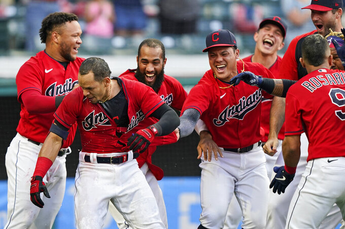 Teammates mob Cleveland Indians' Cesar Hernandez, second from left, after Hernandez hit a two-run home run in the 10th inning of a baseball game against the Minnesota Twins, Saturday, May 22, 2021, in Cleveland. (AP Photo/Tony Dejak)