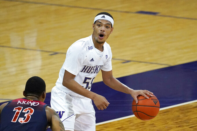 Washington's Quade Green works the ball against Arizona's James Akinjo (13) during the first half of an NCAA college basketball game Thursday, Dec. 31, 2020, in Seattle. (AP Photo/Elaine Thompson)