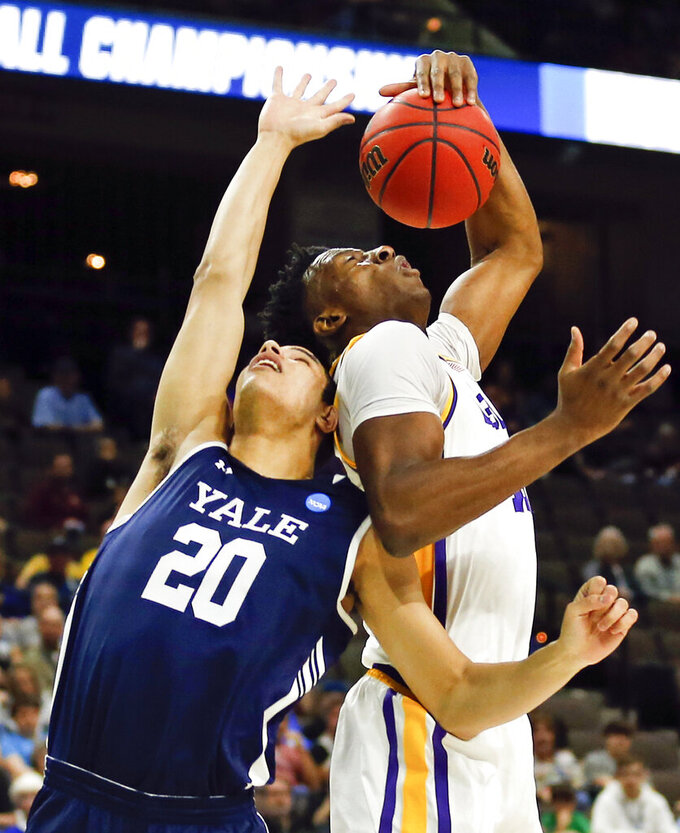 Yale 's Paul Atkinson (20) and LSU's Kavell Bigby-Williams battle for a rebound during the first half of a first round men's college basketball game in the NCAA Tournament in Jacksonville, Fla. Thursday, March 21, 2019. (AP Photo/Stephen B. Morton)