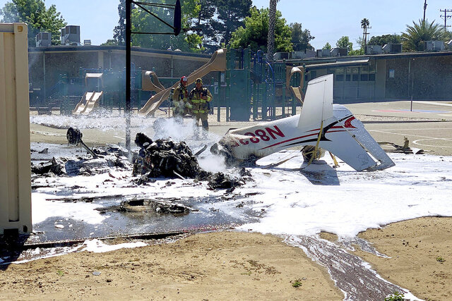 This photo from KEYT/KCOY-TV shows the wreakage of a small plane after it crashed and burst into flames on the grounds of a school in Orcutt, Calif., in Santa Barbara County in Southern California. County authorities say the single-engine Cirrus SR20 landed upside down on a basketball court outside Ralph Dunlap Elementary in Orcutt. The school was closed at the time and nobody on the ground was hurt. The pilot, the plane's only occupant, died at the scene. (Donald Weiting/KEYT/KCOY-TV via AP)
