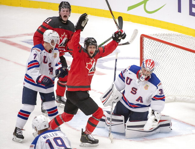 Canada's Dylan Cozens, centre, and teammate Alexis Lafreniere (11) react after the third goal on the United States goaltender Spencer Knight as teammates Spencer Stastney(7) and K'Andre Miller(19) look on during second period at the World Junior Hockey Championships in Ostrava, Czech Republic, Thursday, Dec. 26, 2019. (Ryan Remiorz/The Canadian Press via AP)