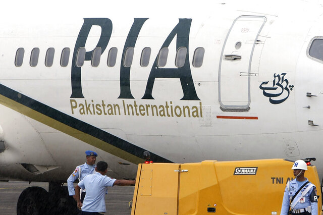 FILE - In this March 7, 2011, file photo, a Pakistan International Airlines passenger jet is parked on the tarmac at a military base in Makassar, Indonesia. The U.S. is downgrading Pakistan's aviation safety rating, a move that blocks that country's airlines from operating flights to the U.S. The Federal Aviation Administration didn't give details behind its action, announced Wednesday, July 15, 2020, but Pakistan has been roiled by a scandal over pilots getting improper licenses. (AP Photo/File)