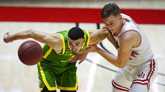 Oregon guard Chris Duarte, left, and Utah guard Pelle Larsson, right, vie for the ball during the second half of an NCAA college basketball game Saturday, Jan. 9, 2021, in Salt Lake City. (AP Photo/Rick Bowmer)