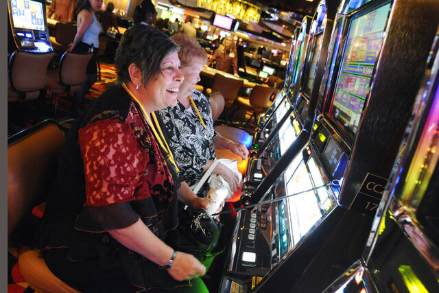 FILE - In this July 15, 2011 file photo, patrons plays the slots during a special VIP event at the new Rivers Casino in Des Plaines, Ill.  Even though Illinois lawmakers have finally approved a Chicago casino, the city faces major obstacles before anyone can place any bets. One of the biggest issues is trying to make it more profitable. Lawmakers adjourned their veto session this month without addressing the issue. Mayor Lori Lightfoot says they'll try again in January. (Mark Welsh/Daily Herald via AP, File)