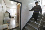 "Kim Da-hye, a 29-year-old South Korean, comes down the stairs to enter her semi-basement apartment in Seoul, South Korea, Saturday, Feb. 15, 2020. For many South Koreans, the image of a cramped basement apartment portrayed in the Oscar-winning film ""Parasite"" rings true, bringing differences in their social status to worldwide attention. (AP Photo/Ahn Young-joon)"