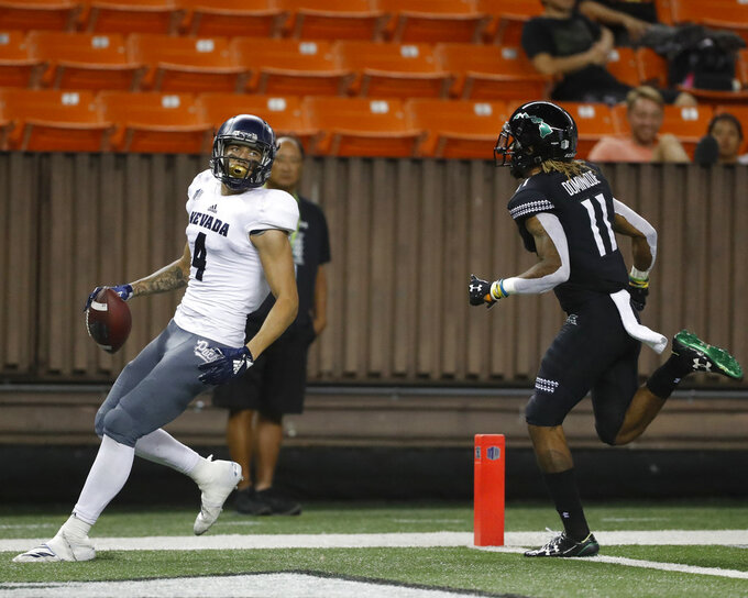 Nevada wide receiver Elijah Cooks (4) makes a touchdown as Hawaii defensive back Jay Dominique (11) runs during the third quarter at an NCAA college football game Saturday, Oct. 20, 2018, in Honolulu. (AP Photo/Marco Garcia)