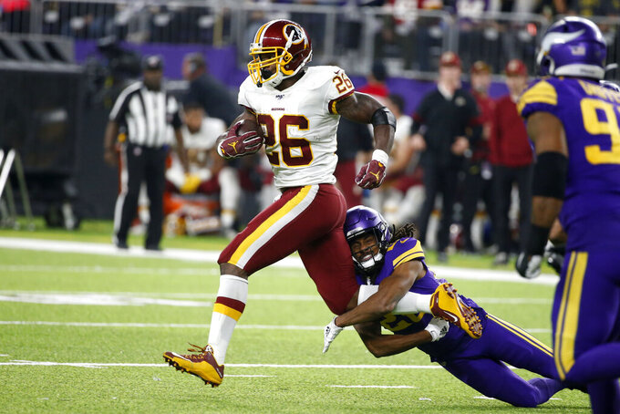 Washington Redskins running back Adrian Peterson (26) is tackled by Minnesota Vikings cornerback Trae Waynes during the second half of an NFL football game, Thursday, Oct. 24, 2019, in Minneapolis. (AP Photo/Bruce Kluckhohn)