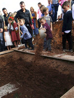 Children shovel dirt into the grave that contains the remains of Christina Langford Johnson the last victim of a cartel ambush that killed nine American women and children earlier this week, during a burial service in Colonia LeBaron, Mexico, Saturday, Nov. 9, 2019. In the attack Monday, Langford Johnson jumped out of her vehicle and waved her hands to show she was no threat to the attackers and was shot twice in the heart, community members say. Her daughter Faith Marie Johnson, 7 months old, was found unharmed in her car seat. (AP Photo/Marco Ugarte)