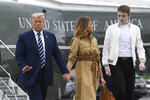 FILE - In this Aug. 16, 2020 file photo, President Donald Trump, first lady Melania Trump and their son, Barron Trump, walk off of Marine One and head toward Air Force One at Morristown Municipal Airport in Morristown, N.J. (AP Photo/Susan Walsh)