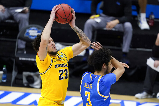 Michigan forward Brandon Johns Jr. (23) shoots on UCLA Bruins guard Johnny Juzang (3) during the first half of an Elite 8 game in the NCAA men's college basketball tournament at Lucas Oil Stadium, Tuesday, March 30, 2021, in Indianapolis. (AP Photo/Darron Cummings)