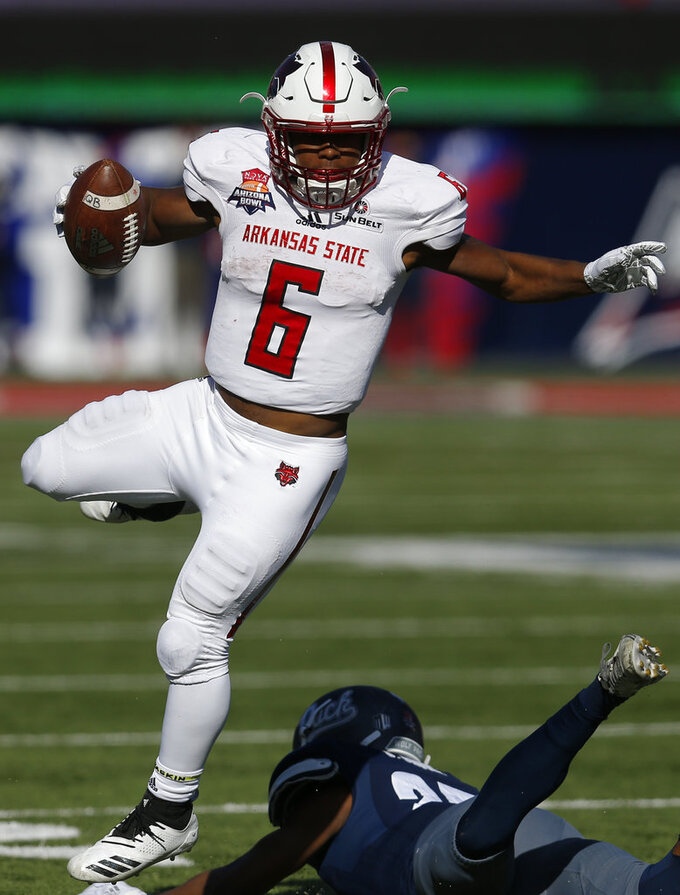 Arkansas State running back Warren Wand (6) avoids the tackle by Arkansas State defensive back Jeremy Smith in the second half half of the Arizona Bowl NCAA college football game Saturday, Dec. 29, 2018, in Tucson, Ariz. (AP Photo/Rick Scuteri)
