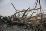 A worker walks among the wreckage of a vehicle oil store hit by Saudi-led airstrikes in Sanaa, Yemen, Thursday, July 2, 2020. (AP Photo/Hani Mohammed)
