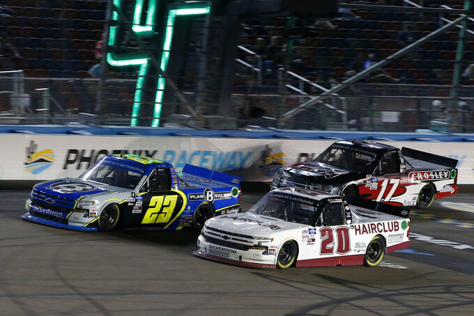 Brett Moffitt (23) races Spencer Boyd (20) and Dylan Lupton (17) through Turn 4 during the NASCAR Truck Series auto race at Phoenix Raceway, Friday, Nov. 6, 2020, in Avondale, Ariz. (AP Photo/Ralph Freso)