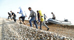 A group of people thought to be migrants run from an inflatable boat at Kingsdown beach where they arrived after crossing the English Channel, near Dover, Kent, England, Monday, Sept. 14, 2020. (Gareth Fuller/PA via AP)