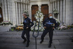 Municipal policemen stand guard outside Notre Dame church in Nice, France, Friday, Oct. 30, 2020. A new suspect is in custody in the investigation into a gruesome attack by a Tunisian man who killed three people in a French church. France heightened its security alert amid religious and geopolitical tensions around cartoons mocking the Muslim prophet. (AP Photo/Daniel Cole)
