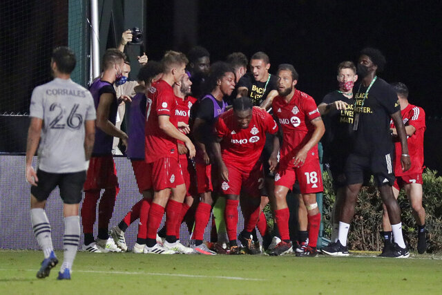 Toronto FC forward Ayo Akinola, center, celebrates with teammates after scoring his third goal of the game during the second half of an MLS soccer match the Montreal Impact, Thursday, July 16, 2020, in Kissimmee, Fla. (AP Photo/John Raoux)