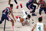 Boston Celtics' Vincent Poirier tries to pass while falling during the second half of an NBA basketball game against the Washington Wizards Thursday, Aug. 13, 2020 in Lake Buena Vista, Fla. (AP Photo/Ashley Landis, Pool)