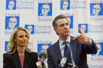"""FILE - In this March 28, 2019, file photo, California Gov. Gavin Newsom with his wife, Jennifer Siebel Newsom attend a roundtable discussion with Central American community leaders at the Clinica Monsenor Oscar Romero in Los Angeles. Gov. Newsom said he """"absolutely"""" sees no conflict of interest with a nonprofit launched by his wife accepting donations from companies that lobby his administration. He was responding to a reporter in The Sacramento Bee that found The Representation Project, the nonprofit launched by Jennifer Siebel Newsom, received at least $800,000 from corporations that lobby state government. (AP Photo/Damian Dovarganes, File)"""