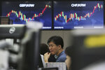 A currency trader watches monitors at the foreign exchange dealing room of the KEB Hana Bank headquarters in Seoul, South Korea, Friday, Aug. 7, 2020. Asian shares were mostly lower Friday in lackluster trading, as the region weighed continuing trade tensions over China and optimism about more fiscal stimulus for the ailing U.S. economy. (AP Photo/Ahn Young-joon)