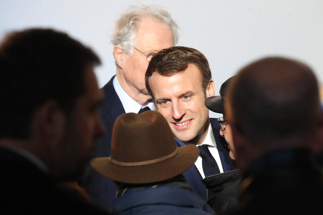 French President Emmanuel Macron, center, meets members of the Jewish community during a ceremony to inaugurate the renovated Wall of Names. Monday, Jan. 27, 2020 at the Shoah memorial in Paris. (AP Photo/Michel Euler, Pool)