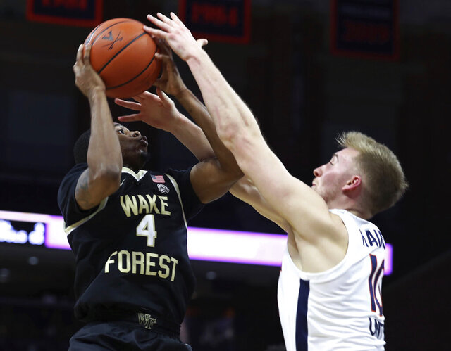 Wake Forest guard Daivien Williamson (4) is defended by Virginia's Sam Hauserof an NCAA college basketball game Wednesday, Jan. 6, 2021, in Charlottesville, Va. (Erin Edgerton/The Daily Progress via AP, Pool)