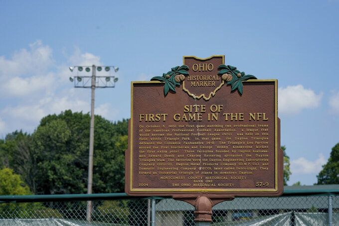 A plaque commemorating the site of the first NFL football game stands in Triangle Park, Saturday, July 27, 2019, in Dayton, Ohio. (AP Photo/Bryan Woolston)