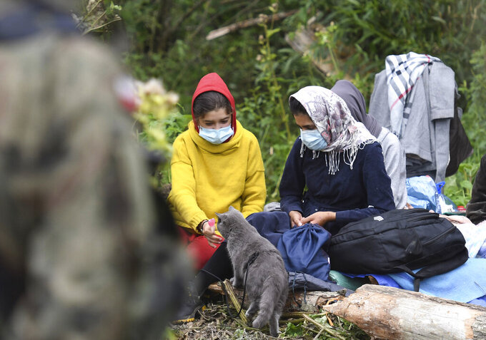 Migrants wait in an area between the borders of Belarus and Poland near the village of Usnarz Gorny, Poland, on Friday Aug. 20, 2021. A refugee rights group in Poland said Friday that 32 people who fled Afghanistan have been trapped for 12 days in an area between the Polish and Belarusian borders, caught up in a standoff between the two countries. (AP Photo/Michal Kosc)