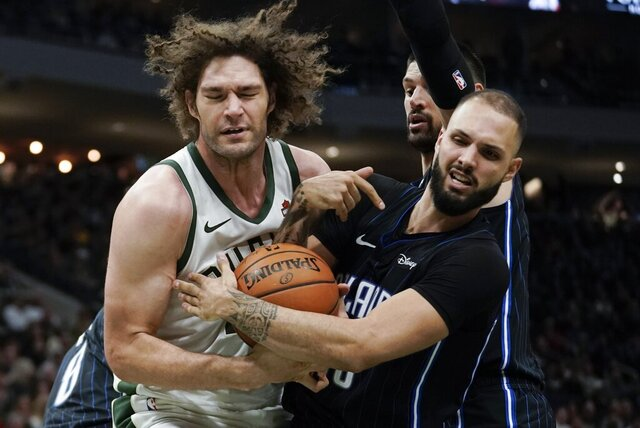 Milwaukee Bucks' Robin Lopez and Orlando Magic's Evan Fournier battle for a rebound during the second half of an NBA basketball game Saturday, Dec. 28, 2019, in Milwaukee. The Bucks won 111-100. (AP Photo/Morry Gash)