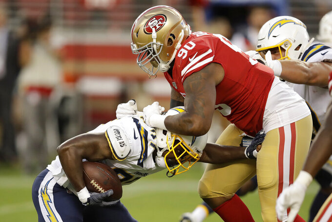San Francisco 49ers defensive tackle Jay Bromley (90) tackles Los Angeles Chargers running back Derrick Gore during the first half of an NFL preseason football game in Santa Clara, Calif., Thursday, Aug. 29, 2019. (AP Photo/Ben Margot)