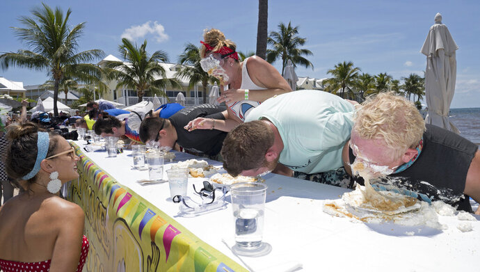 In this photo provided by the Florida Keys News Bureau, contestants in the Mile-High Key Lime Pie Eatin' Contest race to consume a 9-inch pie Thursday, July 4, 2019, in Key West, Fla. The competition, billed as a sweeter alternative to New York's July 4th hotdog-eating clash, was won by Key Wester David Johnson who finished in 58.2 seconds. The event kicked off Key West's Key Lime Festival that continues through Sunday, July 7. (Rob O'Neal/Florida Keys News Bureau via AP)