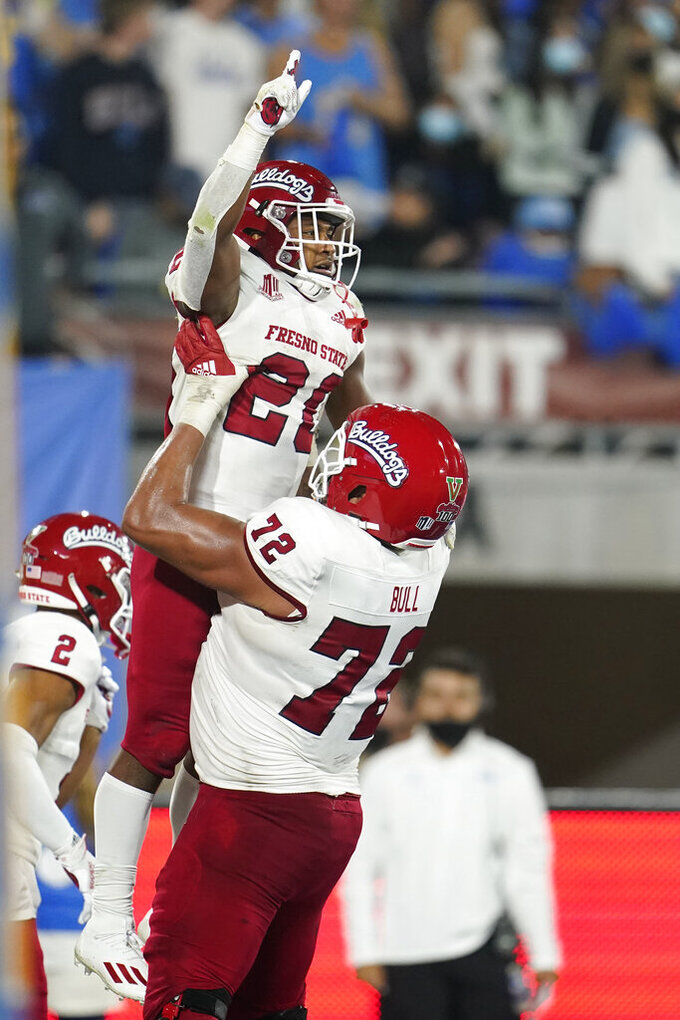 Fresno State running back Ronnie Rivers (20) celebrates his touchdown with offensive lineman Dontae Bull (72) during the first half of an NCAA college football game against UCLA Saturday, Sept. 18, 2021, in Pasadena, Calif. (AP Photo/Marcio Jose Sanchez)