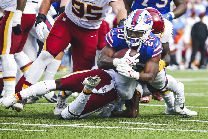 Buffalo Bills' Zack Moss (20) dives past Washington Football Team's Jamin Davis (52) and Kamren Curl (31) during the second half of an NFL football game Sunday, Sept. 26, 2021, in Orchard Park, N.Y. (AP Photo/Jeffrey T. Barnes)