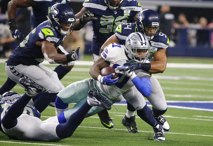 Dallas Cowboys running back Ezekiel Elliott (21) is hit by Seattle Seahawks middle linebacker Bobby Wagner (54) during the second half of the NFC wild-card NFL football game in Arlington, Texas, Saturday, Jan. 5, 2019. (AP Photo/Michael Ainsworth)
