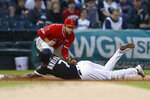 Chicago White Sox's Tim Anderson, bottom, slides safely into third base ahead of a tag by Los Angeles Angels' David Fletcher during the first inning of a baseball game Saturday, Sept. 7, 2019, in Chicago. (AP Photo/Jim Young)
